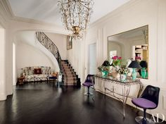 The entrance hall's Jansen balustrade and mirror are original to the Paris apartment of Dior executive Mathilde Favier-Meyer; Knoll chairs flank a console by Gilbert Poillerat | archdigest.com
