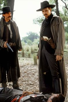TOMBSTONE - Wyatt Earp (Kurt Russell) & Doc Holliday (Val Kilmer) examine the bullet-riddled body of Johnny Ringo (Michael Biehn) Tombstone 1993, Tombstone Movie, Tombstone Quotes, Kurt Russell Tombstone, Scott Eastwood, Hayden Christensen, Harrison Ford, Carrie Fisher, O Cowboy