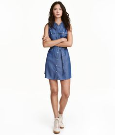 Denim blue. Short dress in soft fabric with buttons at front, chest pockets with flap and button, and concealed side pockets. Tie belt at waist.