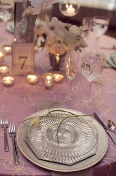 White and radiant orchid (aka lavender) tablescape for a formal gatsby inspired wedding.  flowers on the plates, hanging candles. Formal, lush, romantic. Mercury glass.