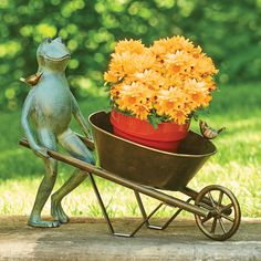 This cute frog is happily pushing his wheelbarrow planter full of beautiful flowers through the garden.