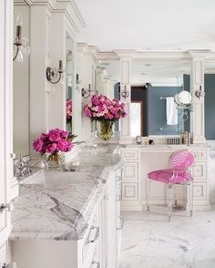A marble and pink bathroom with sweet accents like fresh blooms and the ultimate vanity station. I wish!