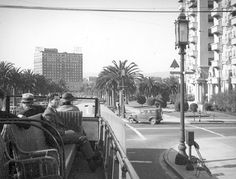 """In this photo, we are treated to the view from atop a double-decker bus, circa 1938. The bus is heading west on Wilshire Blvd and is at the corner of Rampart Blvd. That white building on the right is the Bryson Apartments, whose main claim to fame is that it was featured in Raymond Chandler's 1943 novel """"The Lady in the Lake."""" Built in 1913, it's still there and in fact this view isn't a whole lot different now than it was back then."""