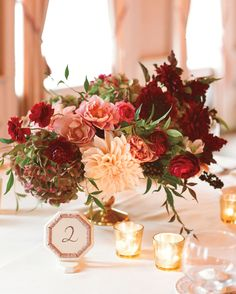 Dinnerplate dahlias (the day's signature bloom), ranunculus, roses, hellebores, and variegated hydrangea in shades of ruby red and soft pinks were arranged in gold pedestal vases and surrounded by gold mercury glass votive holders. Fall Wedding Centerpieces, Fall Wedding Flowers, Fall Wedding Colors, Wedding Flower Arrangements, Floral Centerpieces, Wedding Color Schemes, Floral Wedding, Wedding Decorations, Centerpiece Ideas