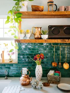 Beautiful kitchen with sea green tiles, plants and a gorgeous wooden tea box.