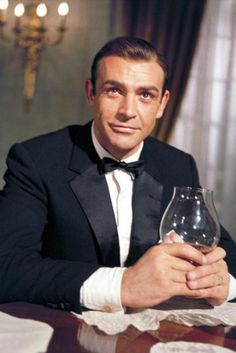 Sean Connery as James Bond in Goldfinger (1964) wearing a midnight blue suit.