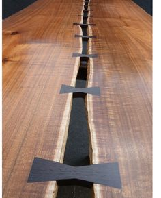 Tim Carney started creating artistic live edge table tops similar to this one, 18 years ago before they became trendy. :-) He cuts the slab lengthwise, then turns the live edges to the center and leaves a gap.