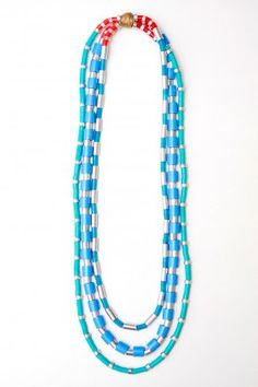 "Turquoise/Coral/Silver--Multi Strand Necklace Shiny silver aluminum mixed with a gradient of aqua blues. Contrasting red and coral accents at back. Waxed hemp knot. Can be worn twisted or untwisted as shown for a layered look. Slips over head. Approximately 13"" long."