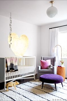 Neutral nursery with gold heart on the wall, bright pillows and purple ottoman.