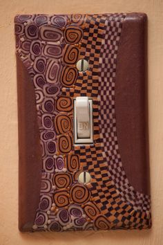 Checkerboard and spiral, purple and mauve and gold, polymer clay glow-in-the-dark switch plate cover. $45.00, via Etsy.