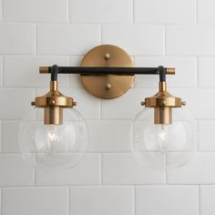 This beautiful mid-century modern vanity light features clear glass globe shades and a mixed metal frame in Matte Black and Antique Gold.