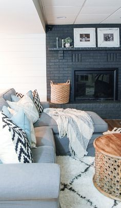 A gorgeous dark gray painted fireplace looks stunning paired with a bright white…