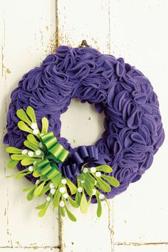 Give the welcoming door wreath, that traditional festive decoration, a bright, modern look. The ruffles are easily made from folded circles of felt pinned in place on a polystyrene base, and then decorated with a machine-stitched mistletoe embellishment. Easy to make ribbon bows add a luxurious touch. #MollieMakes