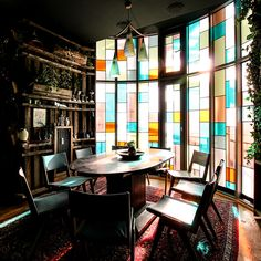 The interior, dotted with vintage curiosities, seems as if it has been put together over time like a patchwork quilt, and looks a little like one too, with its floor-to-ceiling stained glass window feature, wall of mismatched salvaged wooden planks, and ceiling installation of backlit glass panels...