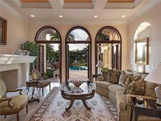 Formal living room with French doors that open to the lanai - fireplace - millwork - ceiling.  Tiburon in Naples, Florida