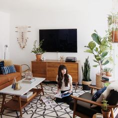 mainly white walls, lots of green plants, pale rug 1 indigo wall possible idea for TV to save space