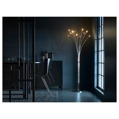 A dark dining room with a lit floor lamp in the corner. The floor lamp has a stainless steel base and at the top sparkling LED lights that looks like fireflies. Ikea Floor Lamp, Floor Lamps, Ikea Lamp, Lampe Decoration, Black Chandelier, Pedestal, Luz Led, Led Lampe, Incandescent Bulbs