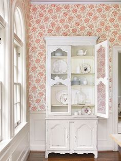 China is displayed behind chicken wire in a painted cupboard - Traditional Home®  Photo: Emily Followill Design: Lillian August