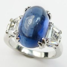 Sugarloaf: A 7.28ct cabochon sapphire glows with an otherworldly blue from between two colorless fancy cut diamonds.  Ca.1938.  Maloys.com