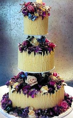 Fancy three level wedding cake. Each tier is round and covered with white chocolate flutes. Decorated with many purple, pink, cream flowers and blue butterflies