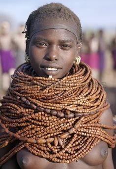 Africa | A Nyag'atom woman wears numerous strands of beads made from wood. Omo Valley, Ethiopia | ©John Warburton-Lee