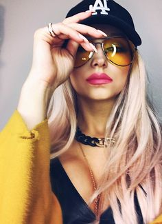 Yellow sunglasses trend yellow coat, streetstyle fashion 2017 bodychain necklace pink lipstick LA hat. Yellow lens shades outfit