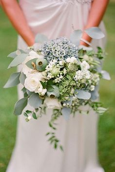 bohemian wedding bouquets cascade bouquet in boho style with white roses and greens in the hands of the bride edward osborn