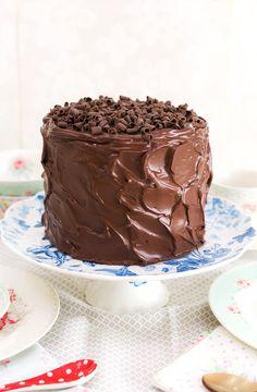 Tarta de chocolate sobre stand para tartas En este vídeo os muestro lo fácil que es hacer una tarta de chocolate rellena y cubierta con ganache. Solamente con un bol y una batidora de mano podemos hacer una mezcla muy chocolateada e irresistible. La podéis hornear en un sólo molde alto, pero con los moldes de layer cake podemos hacer directamente las capas del bizcocho en menor tiempo de horneado. Esto hace que el bizcocho no se reseque y tenga una jugosidad espectacular. La ganache es otra…