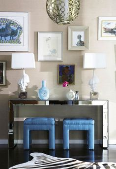 entrances/foyers - mirrored console table white shell lamps blue silk tufted ottomans zebra cowhide rug beige tan grasscloth wallpaper eclectic art gallery