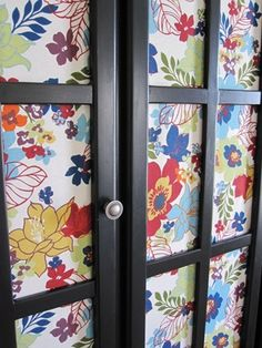 colorful print behind glass door cabinet