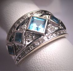 A Stunning Vintage Diamond and Blue Topaz Wedding Ring Band, White Gold Setting. This lovely estate ring holds an array of blue topaz and sparkling white diamonds.