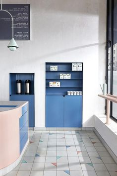 Vacation Café, Melbourne, Australia | White floor tiles with random pastel-coloured triangle corners and elongated steel joinery finished in pink and blue provide the high ceilinged volume with an intimate scale, while slender Mattiazzi chairs and angular Muller van Severen wall lamps add depth #cafe #australia #interiors #interiordesign