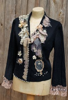 Black vintage linen jacket, has been reworked with intricate details- antique and vintage lace details at bold collarline and hems, mostly handmade dating back 1900. The other details include soft tulle, handpainted antique silk bow, satin sculpted rosebud, vintage french diamante trims and vintage metallic embroidered piece at hem above sepia shade cameo image of baroque lady. Accentuated with hand stitches with cream threads and ivory glassbeads. The waist can be slightly adjusted with…