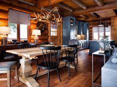 Laid throughout the great room and kitchen, the new wood flooring visually connects and expands the entire space, while shades of gray complement the honey tones of the log walls. - CountryLiving.com