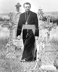 Germans from Russia Heritage Collection - Bishop Joseph Werth of Novosibirsk, Siberia, Russia, visiting a Germans from Russia iron cross cemetery during his first historic tour of North Dakota in the summer of 1993.
