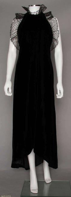 DIOR COUTURE VELVET EVENING DRESS, 1970-1980s  Black velvet, halter neck & cut in shoulders with dotted net flounce.