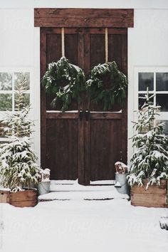 Doubling up on Winter decor with two wreaths and Christmas trees to greet you at your door.