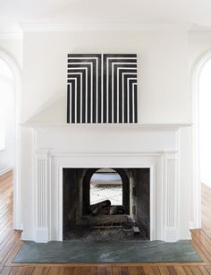 Who wouldn't want this intriguing high contrast black-and-white painting? It's a simple DIY project sure to add a unique contrasting element to any room, especially one with crisp white walls and features such as this one.