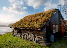 Traditional Warmth. A Norwegian lakeside cabin uses soil and grass on its' roof as insulation - a tradional method of keeping homes warm in Norway. Photo: John & Tina Reid