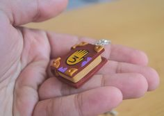 Gravity falls pendants are 1 inch long, very lightweight. It's made out of polymer clay but the details such as the hand 3 is made of paper which is carefully sealed with sculpey glaze.https://www.etsy.com/listing/217204167/gravity-falls-journal-pendants?ref=market