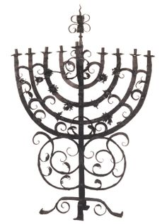 Forged iron Menorah Unmarked, undated, Bohemia, 2nd half of the 18th century Height 1075 mm, width 742 mm This lamp retains the traditional shape of the Menorah's curved branches. It is mainly of interest to the viewer, however, on account of its material – forged iron, which is very rare for such an item. In synagogues, iron tends to be used only for grilles and various structural elements; the most frequent material for Hanukkah menorahs is brass or bronze.