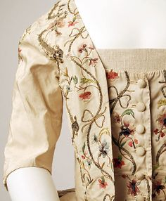 Fashion 18th century gown Caraco dress Robe a la Francaise circa from 1780. Made from silk with metallic embroidered flower floral garland leaf and vines pattern embroidery in various colours decorated  the neckline, matching stomacher at the front bodice and the full skirt hem.