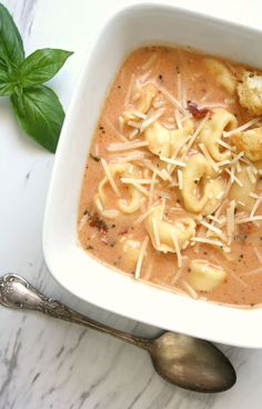 Creamy Tomato Tortellini Soup Recipe garnished with Parmesan cheese, croutons…