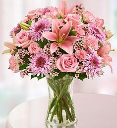 """Going to try and recreate...  Stunning gathering of fresh roses, lilies, cremones, carnations, mini carnations, waxflower and salal in a stylish clear glass gathering vase accented with stylish ribbon; vase measures 8""""H"""