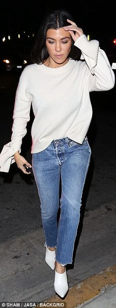 Focused: Kourtney, who added chic pointed white boots, styled her long brunette locks loose in waves
