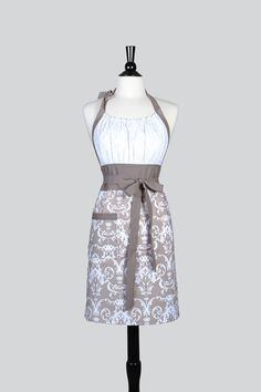 A feminine womens retro aprons in gray and white damask vintage style kitchen apron makes an ideal wedding apron or hostess gift for the woman who loves to cook. An elastic bodice top creates a fitted apron on women of all sizes. Our generous sized lined waist band fits women of all sizes from hip-to-hip for the full figured chef and wrapping more to the back for the petite chef. Long waist ties give you the option of tying your apron in the front or back, whatever suits your fancy…