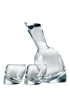 An angled decanter and two matching glasses are fashioned in crystal and feature sturdy, sloping bases.