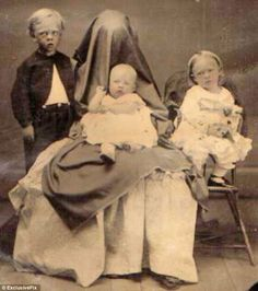 strange vintage family photo……I AM SURE THE YOUNG LAD ON THE LEFT IS A POST-MORTEM………..ccp