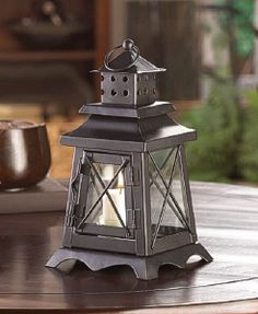 A constant vigil to great design, our Watch Tower Candle Lantern will shine like a beacon inside or out. The black metal frame features a cupola with an over-sized hanging loop at top and classic lighthouse-inspired accents. Place the candle of your choic Lanterns Decor, Hanging Lanterns, Candle Lanterns, Glass Candle, Candle Craft, Candleholders, Lantern Lamp, Lantern Candle Holders, Porta Velas