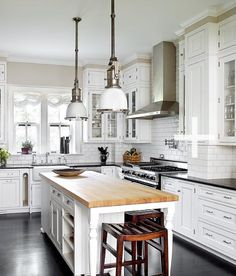 Michael Robinson Photography  crisp white kitchen design with white glass-front kitchen cabinets and black granite countertops, pot filler, white kitchen island with butcher block counter tops, white subway tiles backsplash, farmhouse sink, white island pendant lights, stools and ebony wood floors.